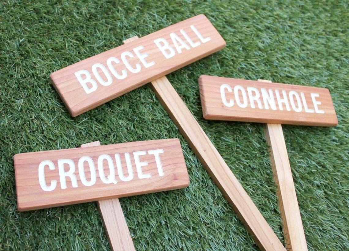 signs that say croquet, bocce ball, and cornhole
