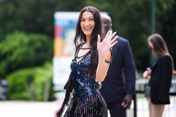 Bella Hadid wears a black and blue shiny sequined dress with fringes, outside Louis Vuitton Parfum hosts dinner at Fondation Louis Vuitton, during Paris Fashion Week - Haute Couture Fall/Winter 2021/2022, on July 05, 2021 in Paris, France