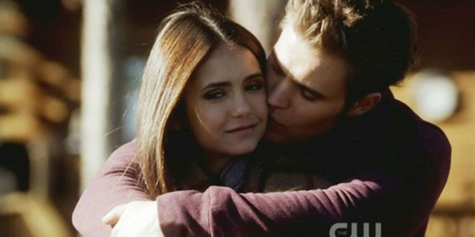 stefan holds elena in a hug from behind and they both have serene looks on their faces, relaxed
