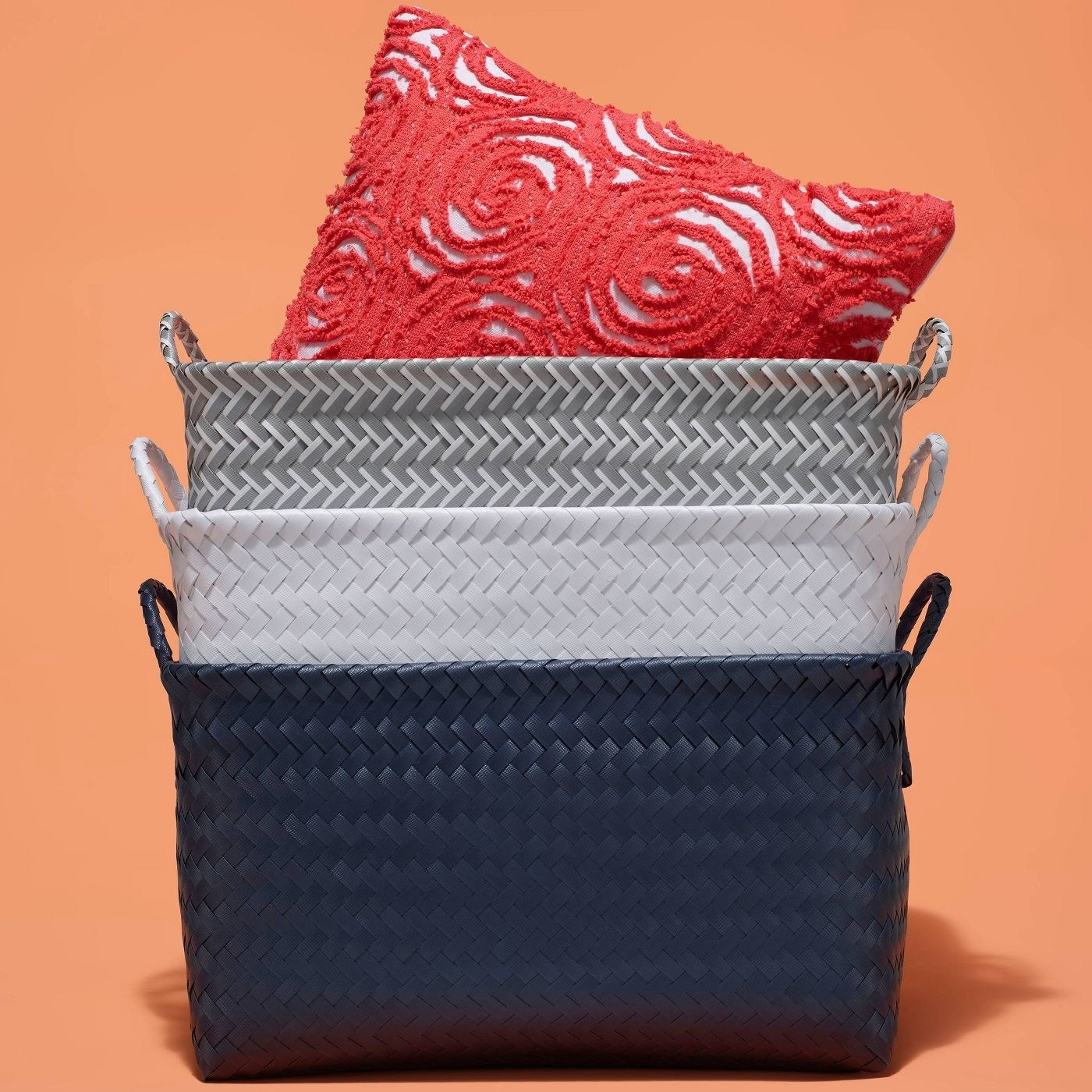 A blue, grey and white basket with a red pillow inside