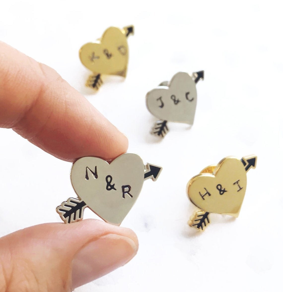 heart shaped pins with arrows going through them and two initials