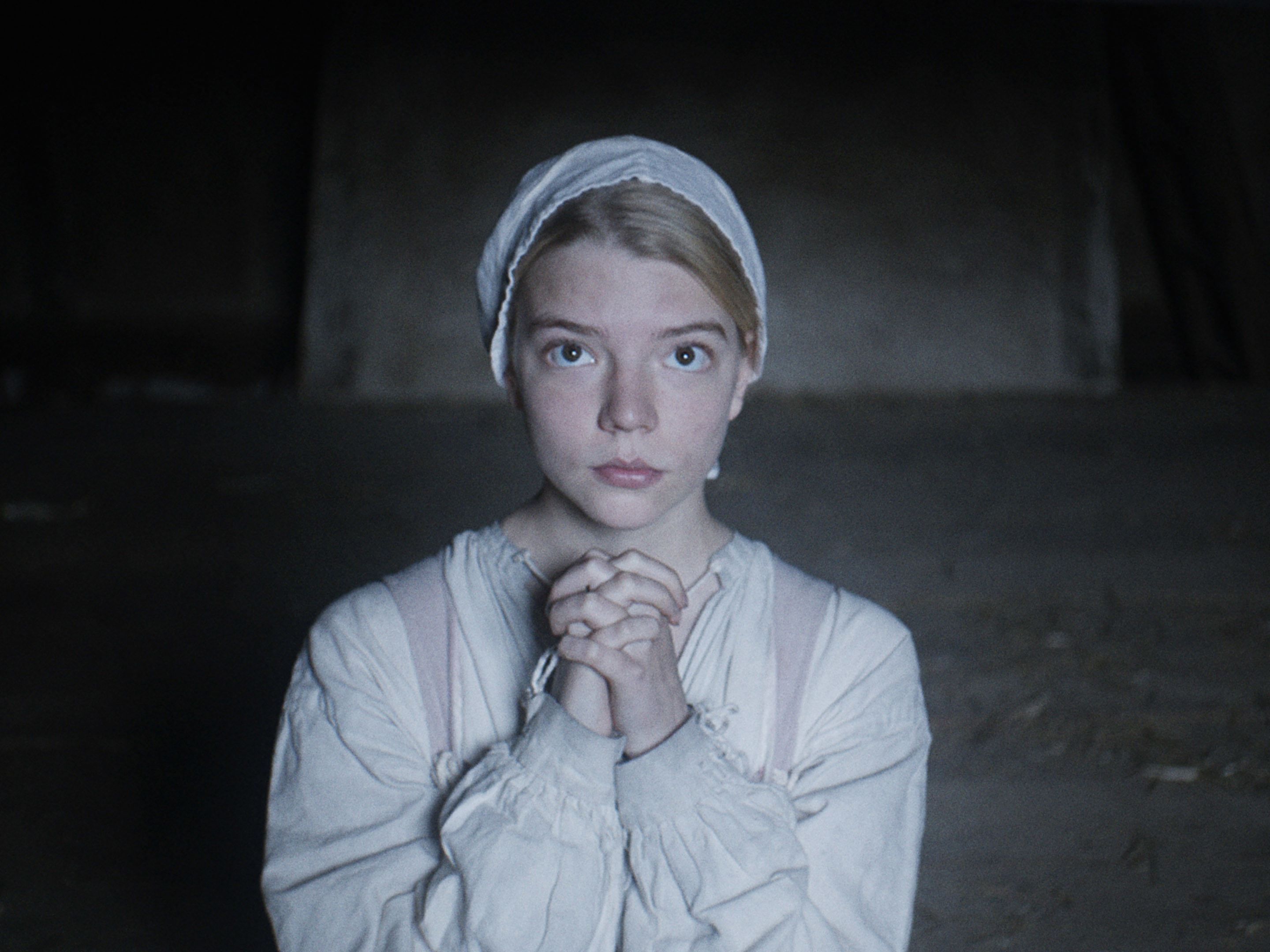 Anya in old new England garb and praying to God that the witch doesn't harm her family
