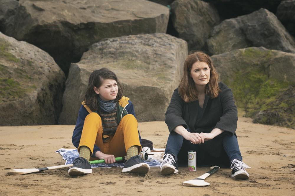 Elijah O'Sullivan and Justine Mitchell sit on a cold beach