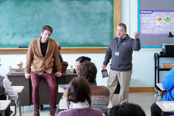 Glenn Howerton and Patton Oswalt stand in front of a class