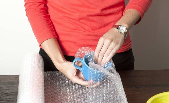 A person packing a ceramic mug in bubble wrap