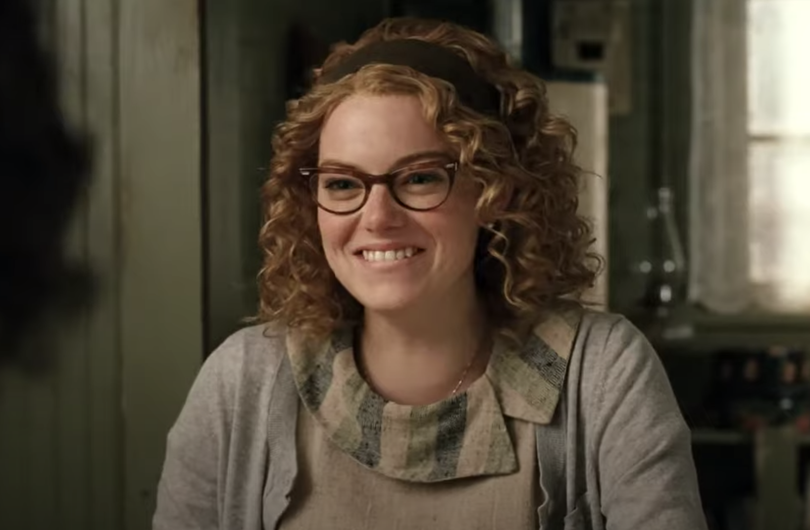 Emma Stone with a short, curly wig