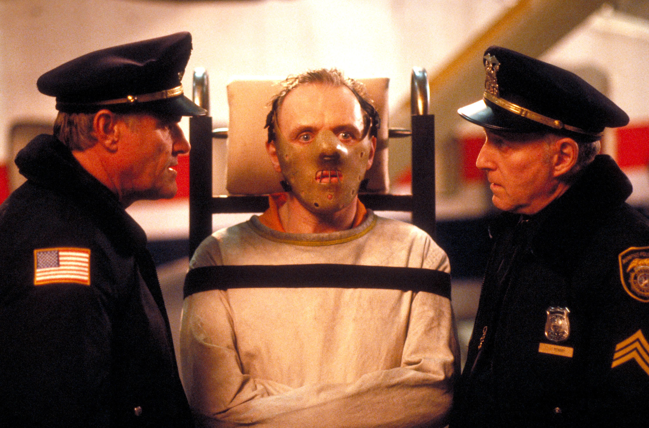 Dr. Lecter strapped onto a gurney in a straight jacket and a hockey mask to prevent him from biting
