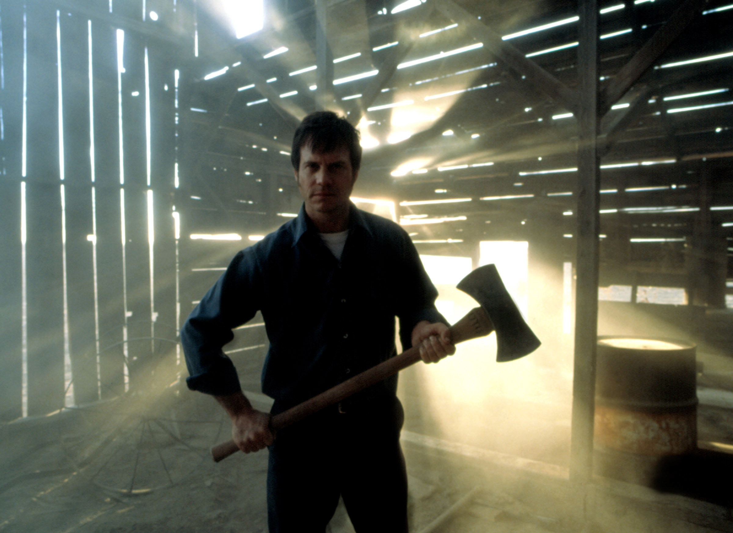 Bill Paxton menacingly wielding a large axe in a spooky barn