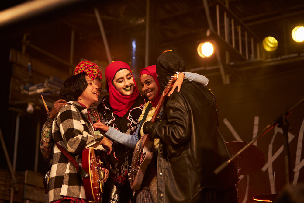 Sarah Kameela Impey, Faith Omole, Juliette Motamed, Anjana Vasan, and Lucie Shorthouse huddle with instruments onstage