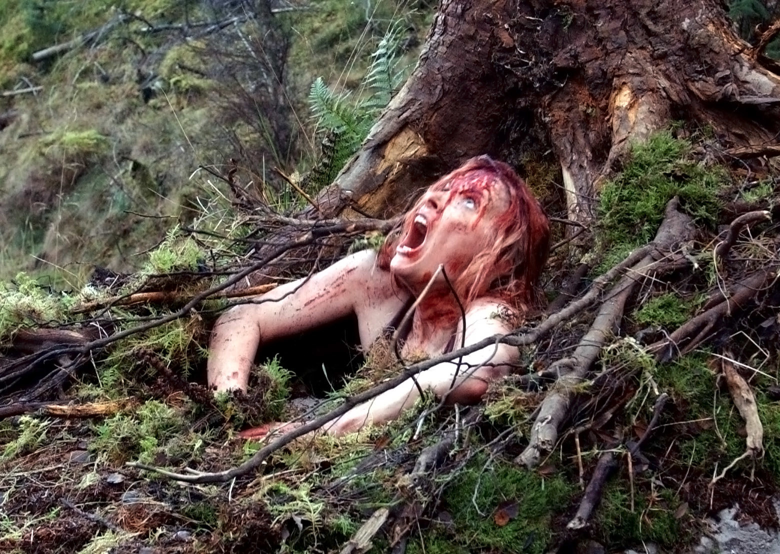 a girl screaming and covered in blood while trying to escape from a cave but being unable to
