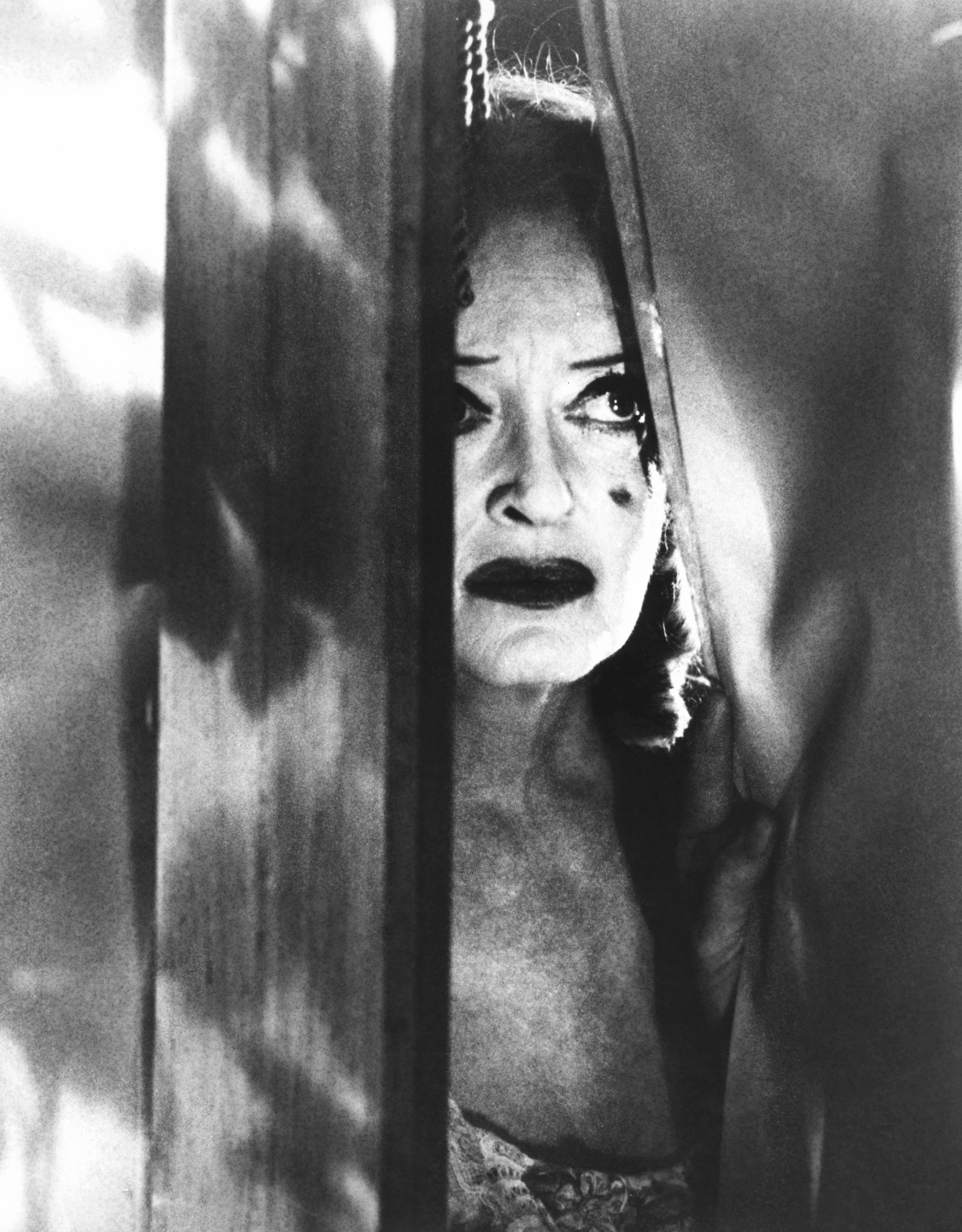 Bette Davis with creepy makeup staring out a window mysteriously