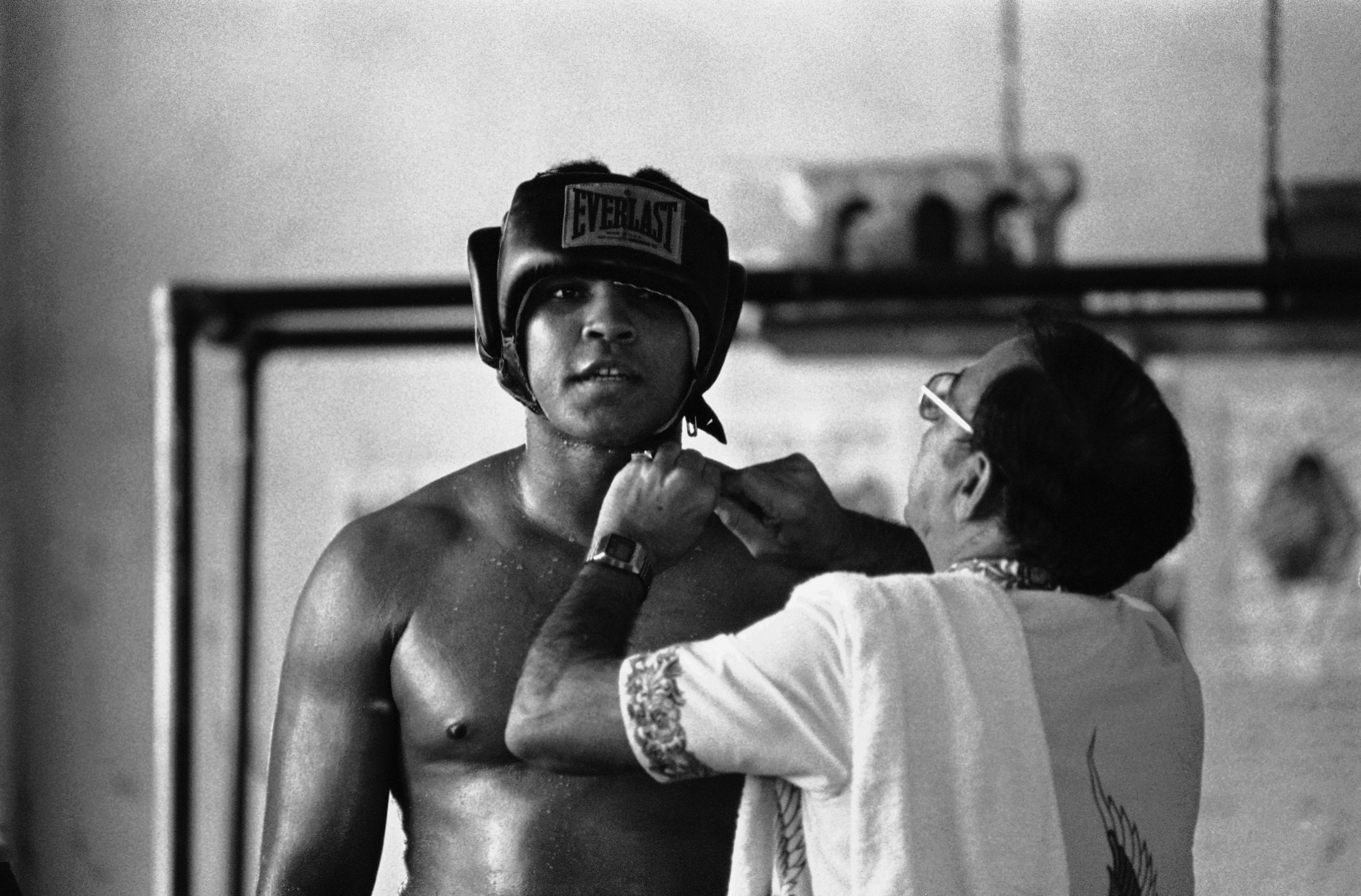 A younger Muhammad Ali being fitted for boxing headgear in a training gym, from the chest up