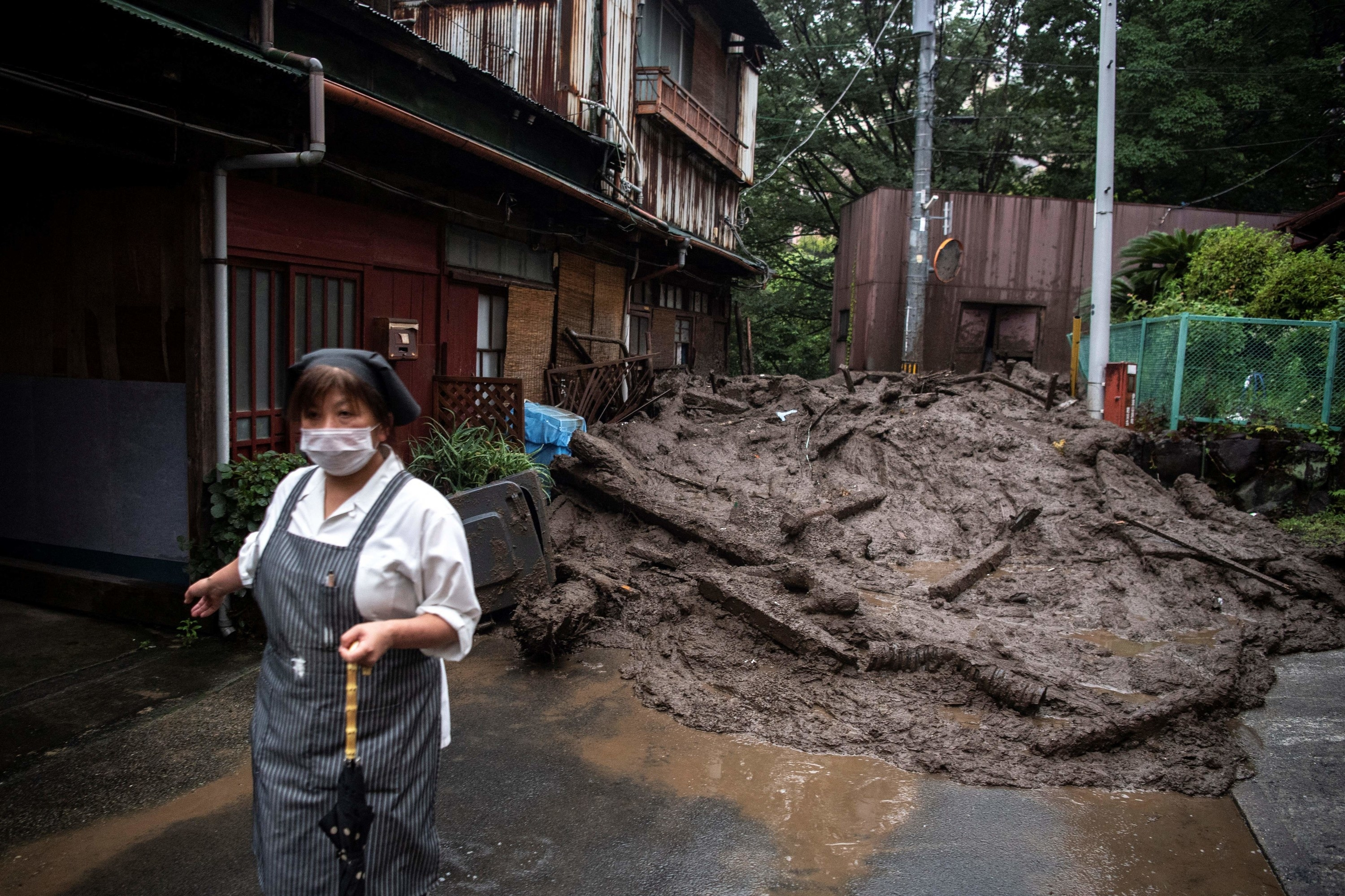 A woman holds an umbrella and stands in front of a giant mudslide in front of houses