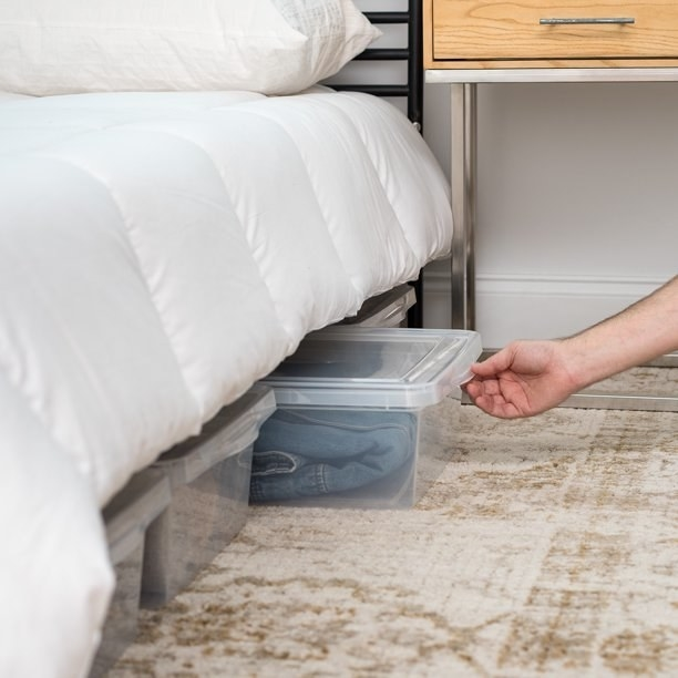 A hand reaching under a bed sliding out one of the clear boxes