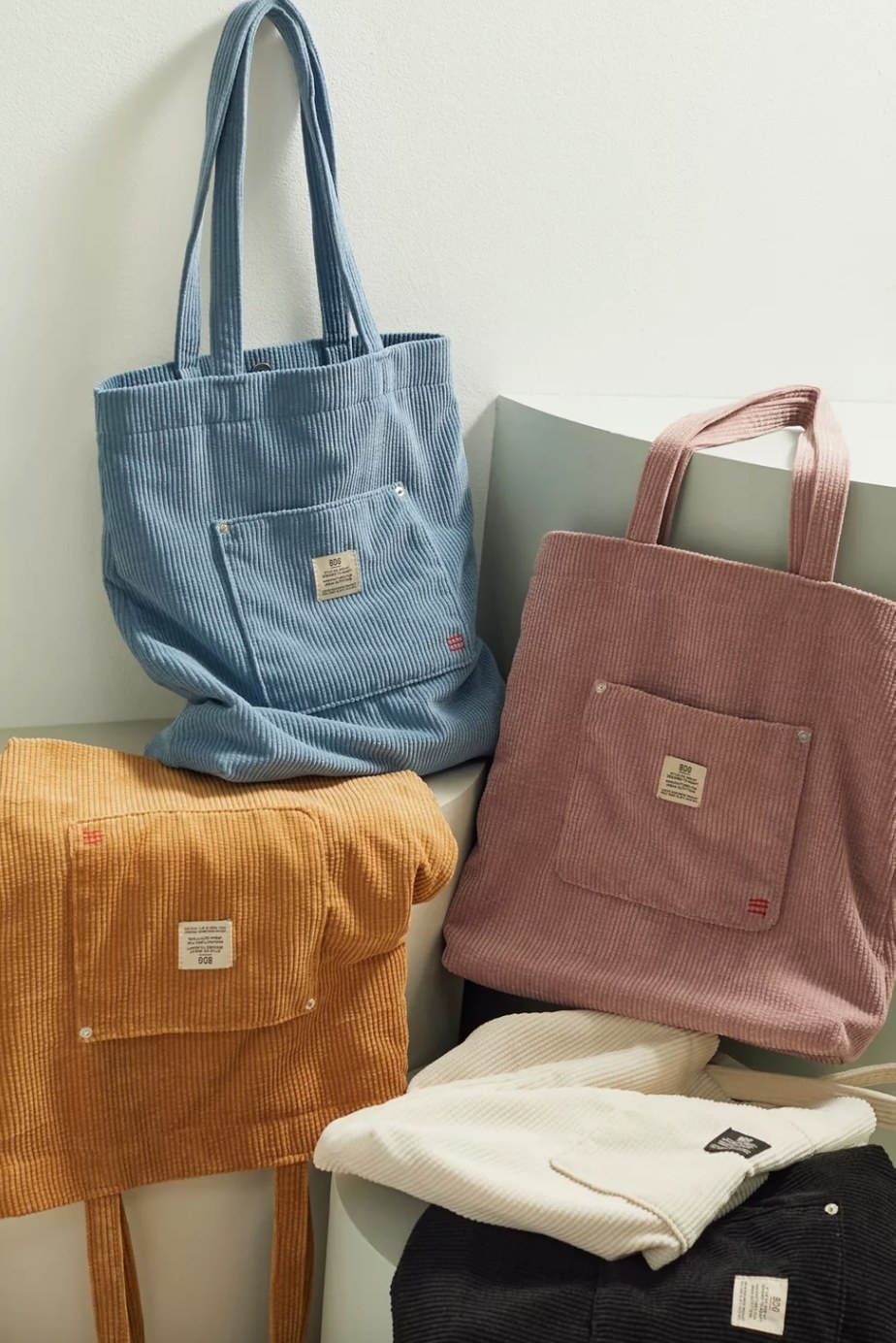the corduroy tote bag in blue, orange, and pink