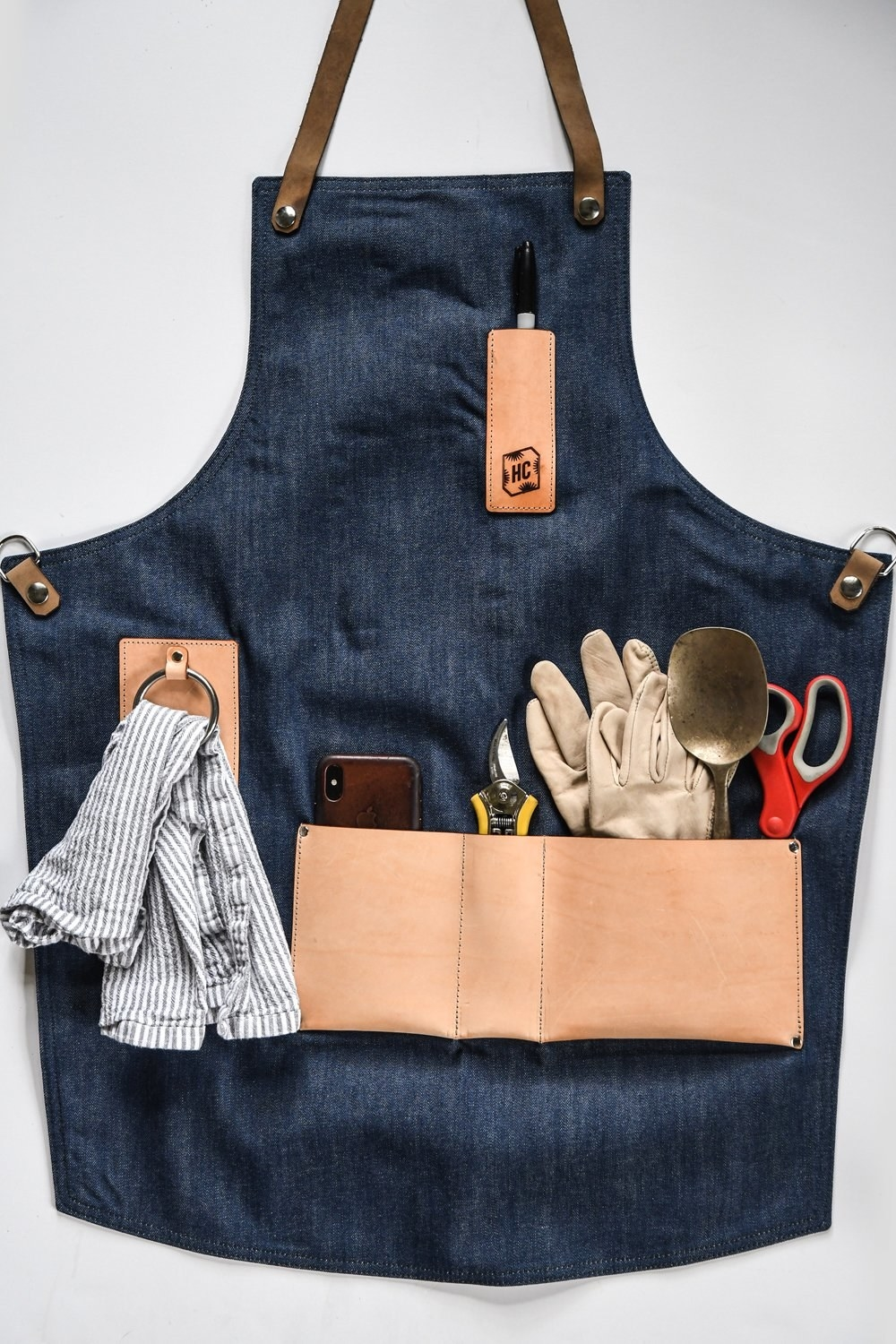 The apron is displayed with all the pockets filled with tools
