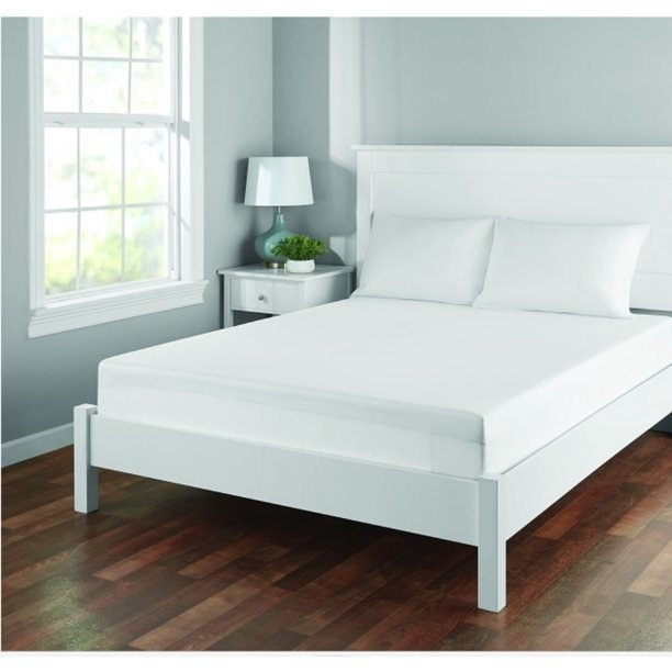 Thewaterproof mattress protector with cooling technology on a white bed frame