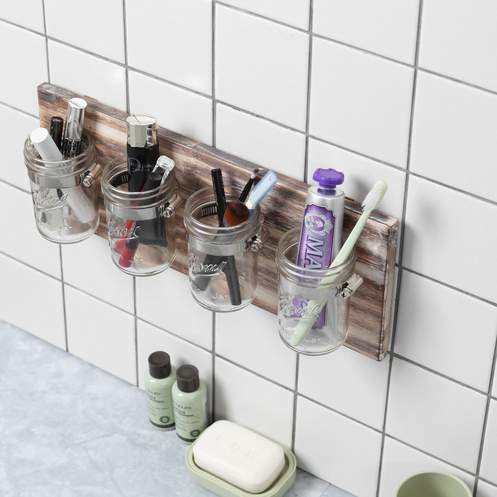 four mason jars mounted on a piece of wood that's attached to a wall