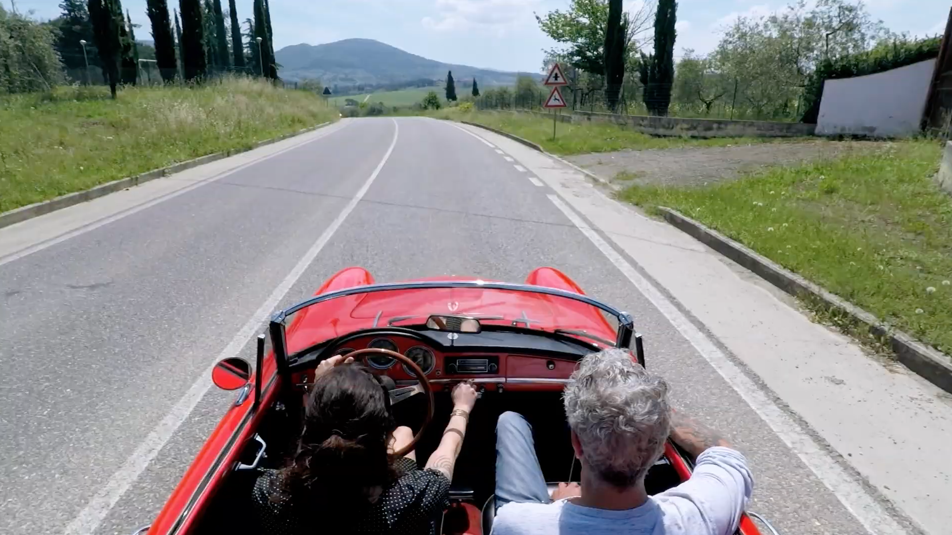 Bourdain riding in a red convertible sports car with Asia Argento