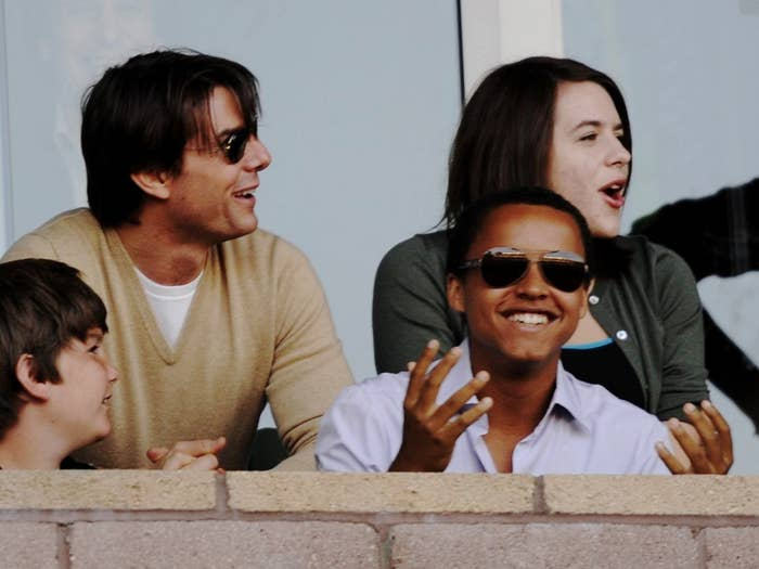 Bella sits in the crowd at a soccer game with Tom and her brother, Connor, many years ago