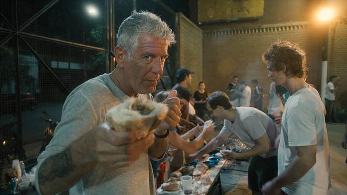 Bourdain holding a cheesesteak sandwich close to the camera
