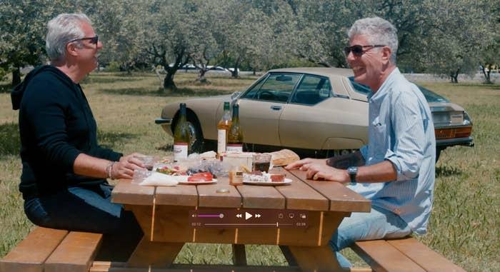 Ripert and Bourdain enjoying a picnic lunch outdoors, sitting on a bench