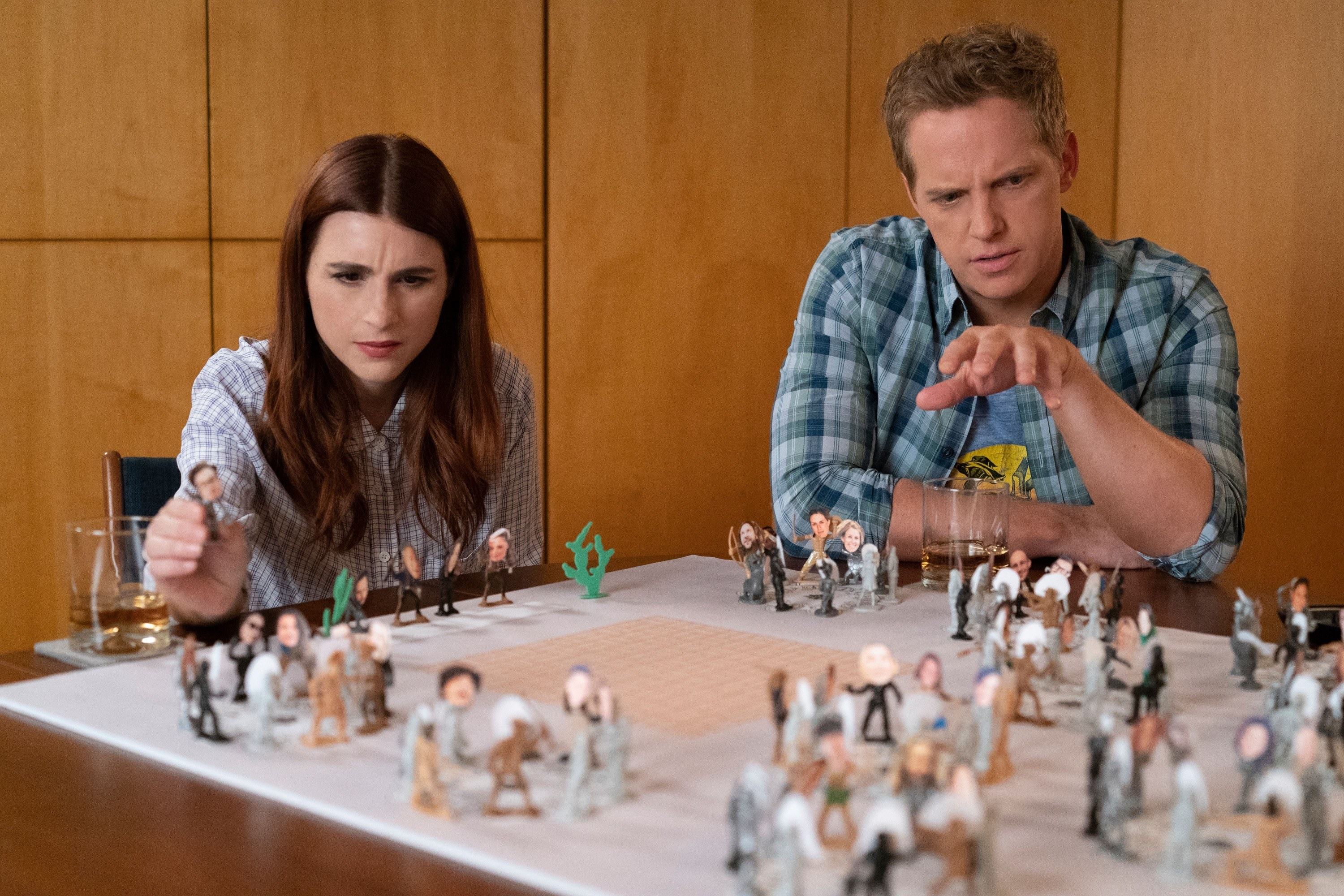 Aya Cash and Chris Geere looking intently at the table
