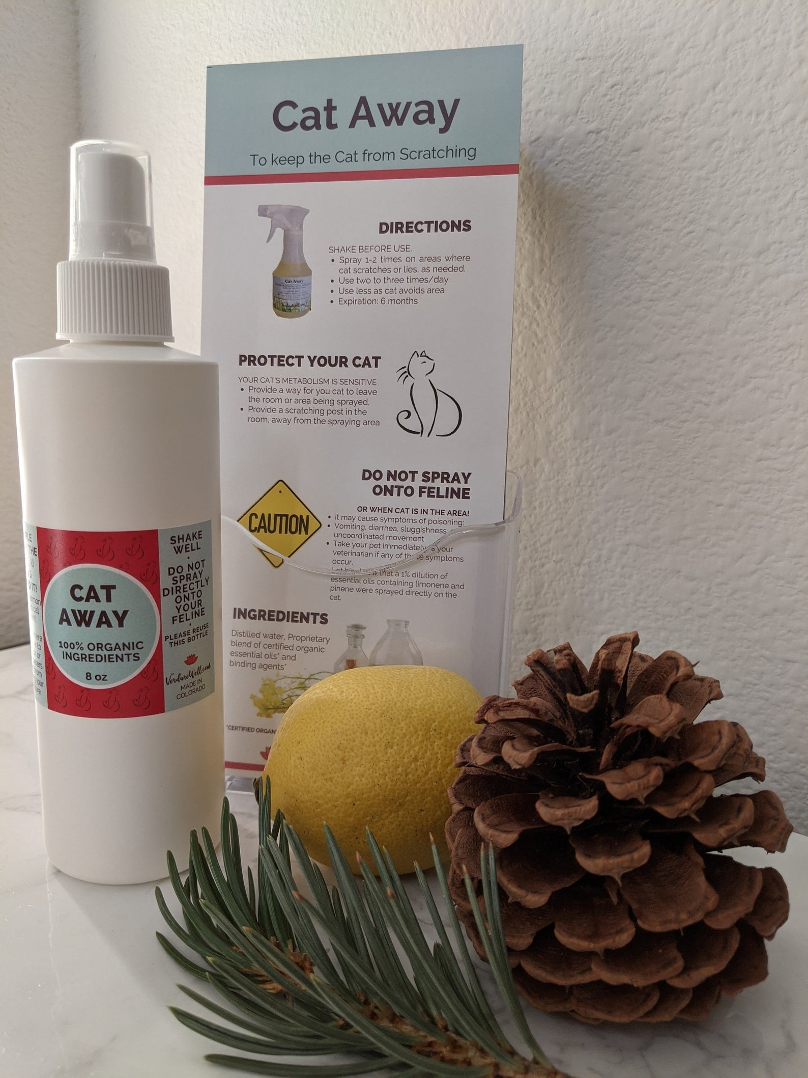 The spray next to a pine cone, spruce, and lemon