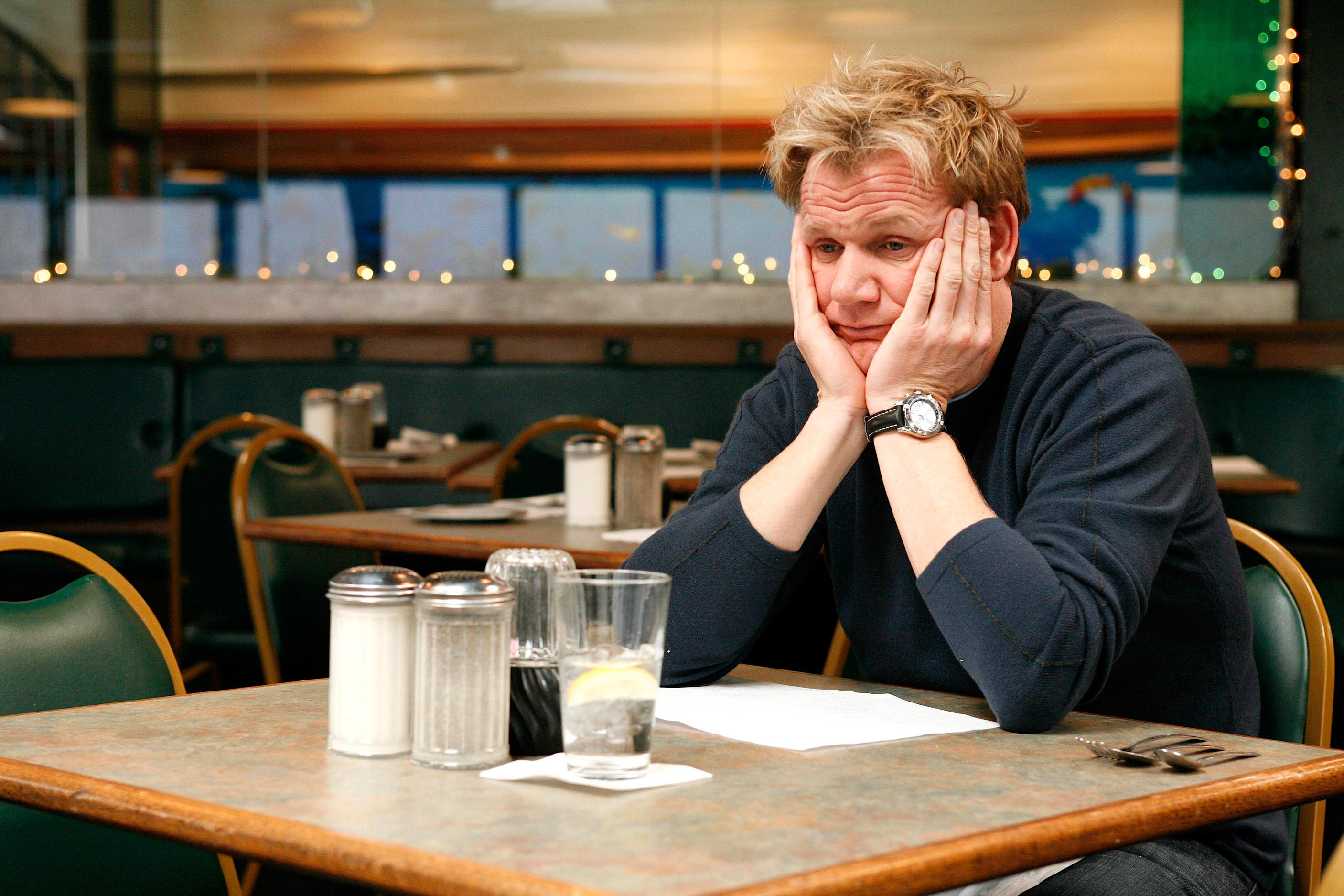 Gordon Ramsay looking sad at a table with his hands holding his face