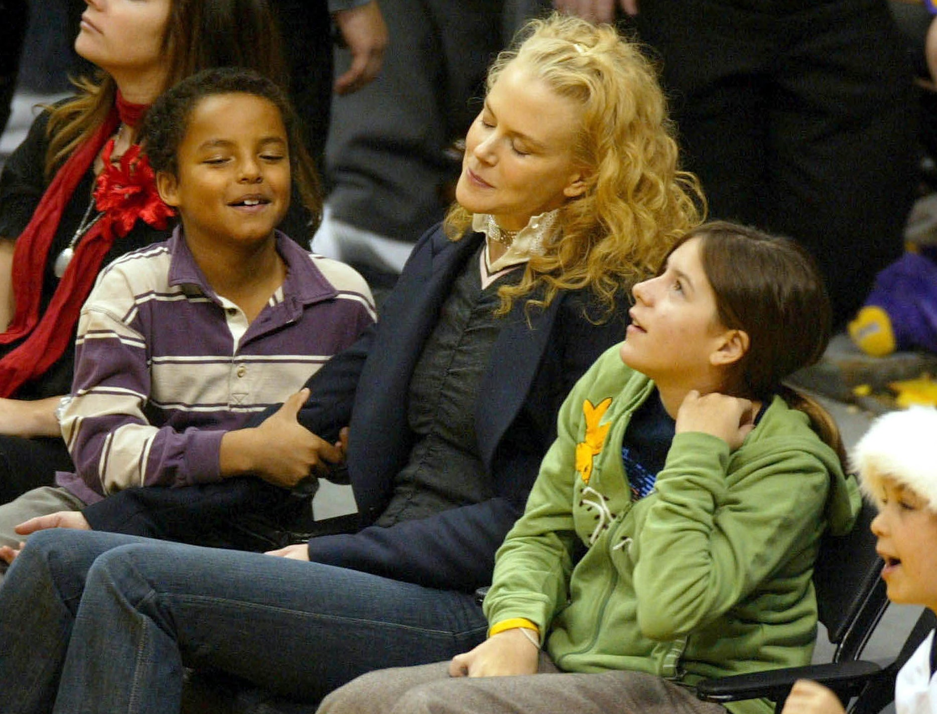 Bella sits next to Nicole and Connor court side at a basketball game