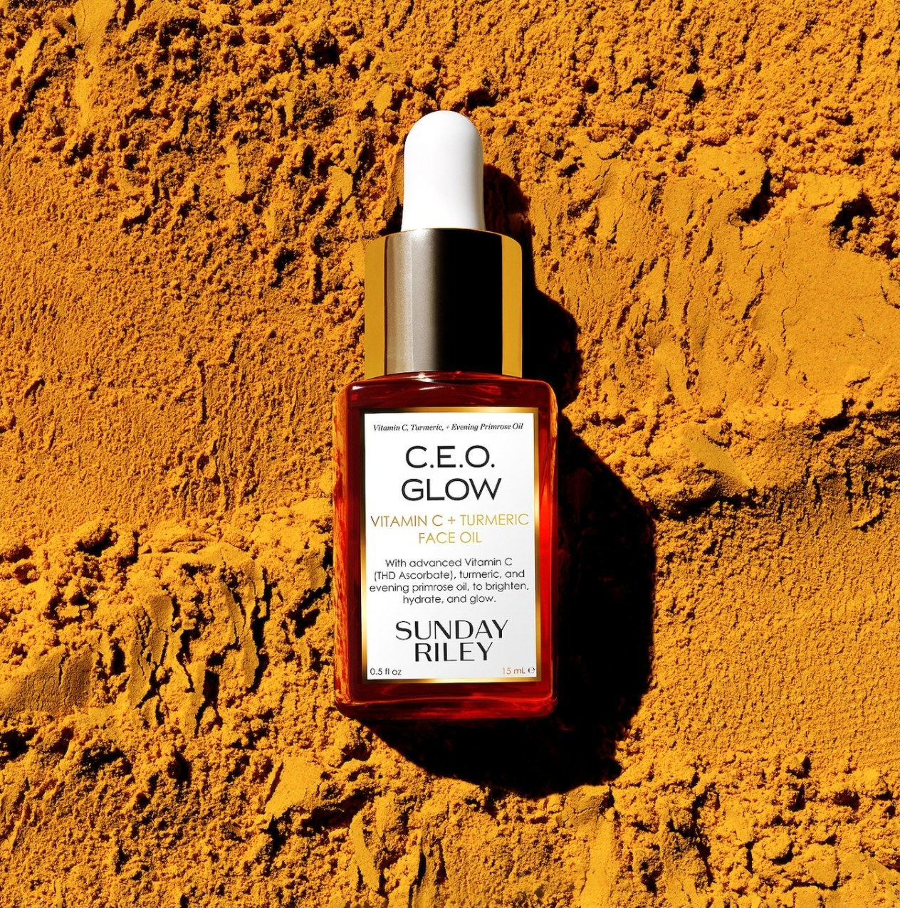 Bottle of Sunday Riley CEO Glow against turmeric powder background