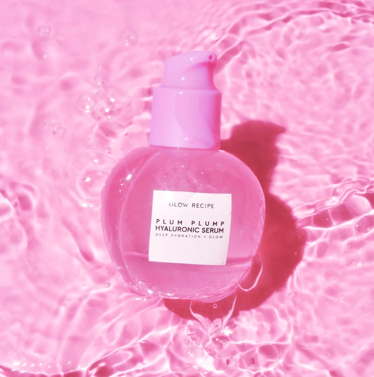 Bottle of glow recipe plum plump against pink water background