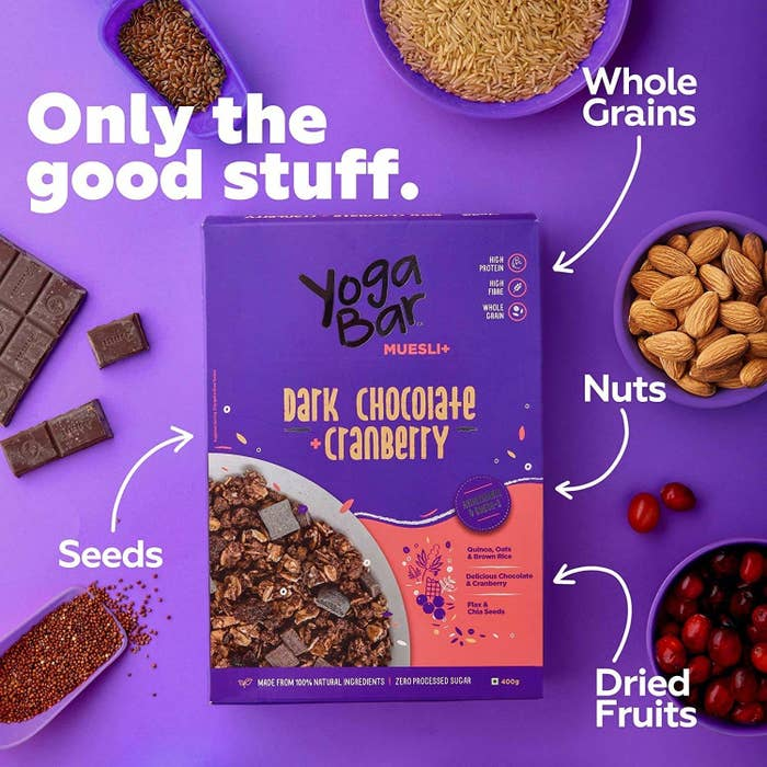 A box of muesli next to cranberry, seeds, dark chocolate, nuts and whole grains