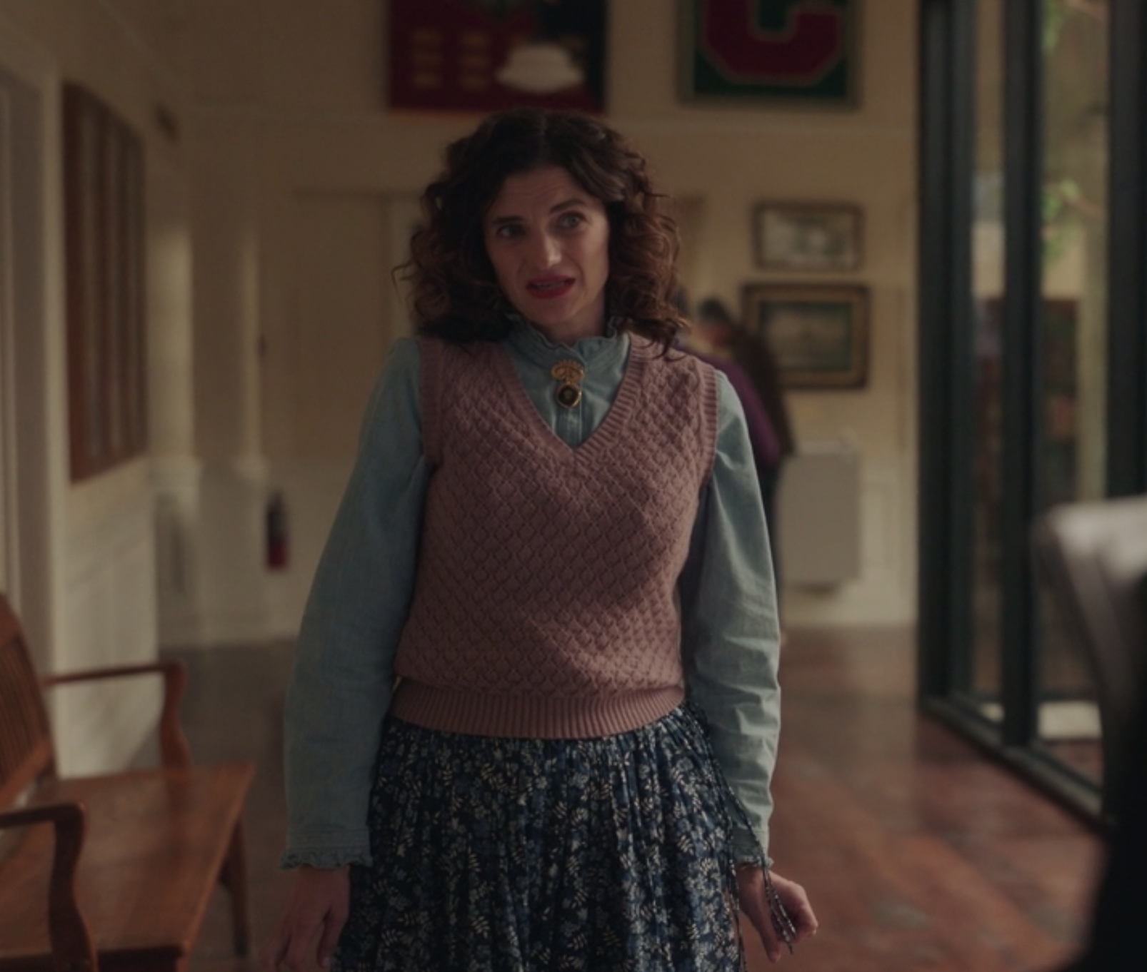 Wendy wears a knit vest over a button up top and a floral skirt