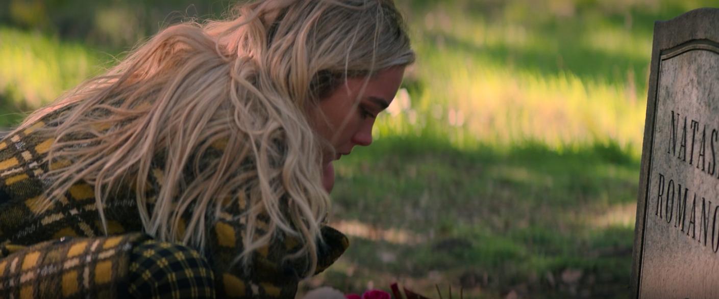 Yelena leaning over Natasha's grave