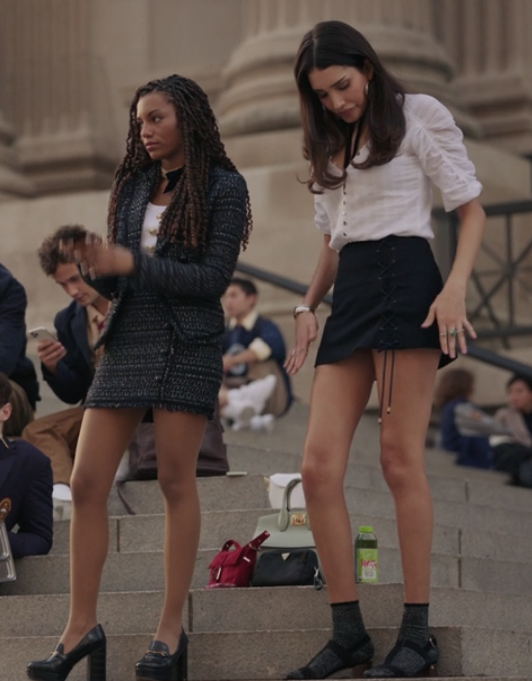 Monet wears a tweed blazer and skirt set and Luna wears a mini skirt with a button up top tucked into it