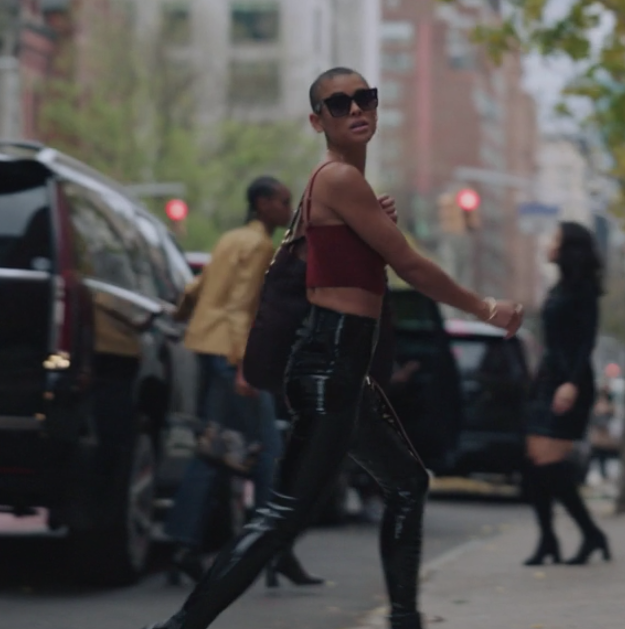 Julien wears high waisted leather pants and a cropped tank top