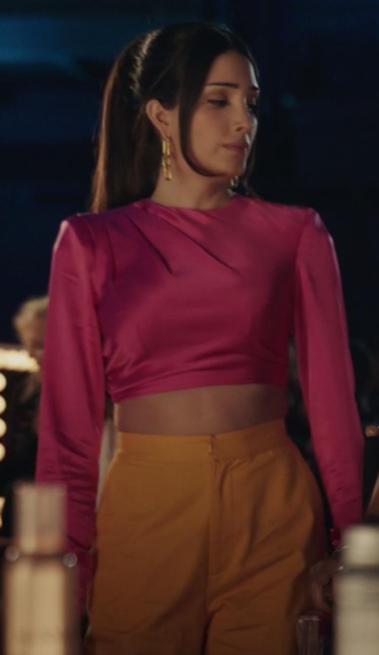 Luna wears a cropped long sleeve pink shirt and high waisted orange pants.