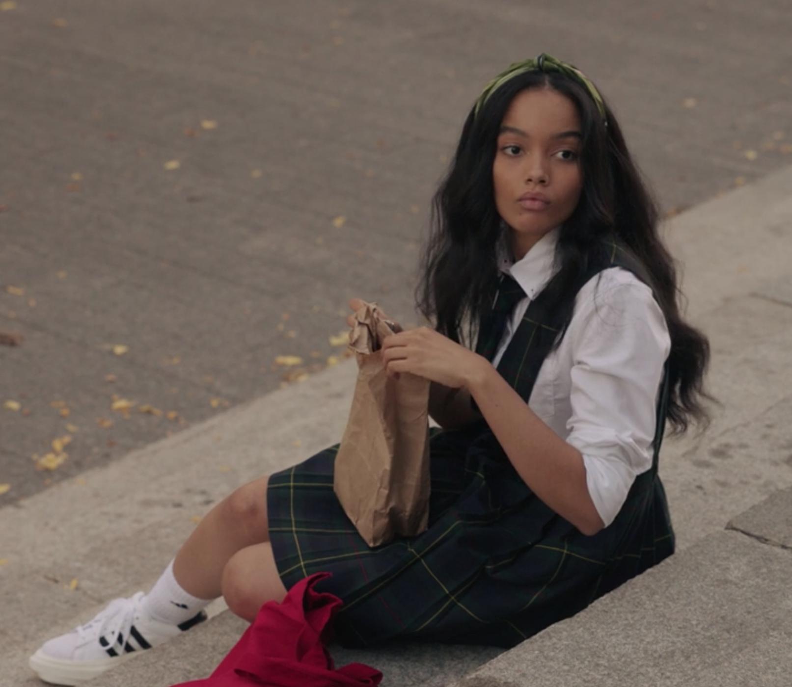 Zoya wears a striped uniform jumper skirt over a long sleeve shirt
