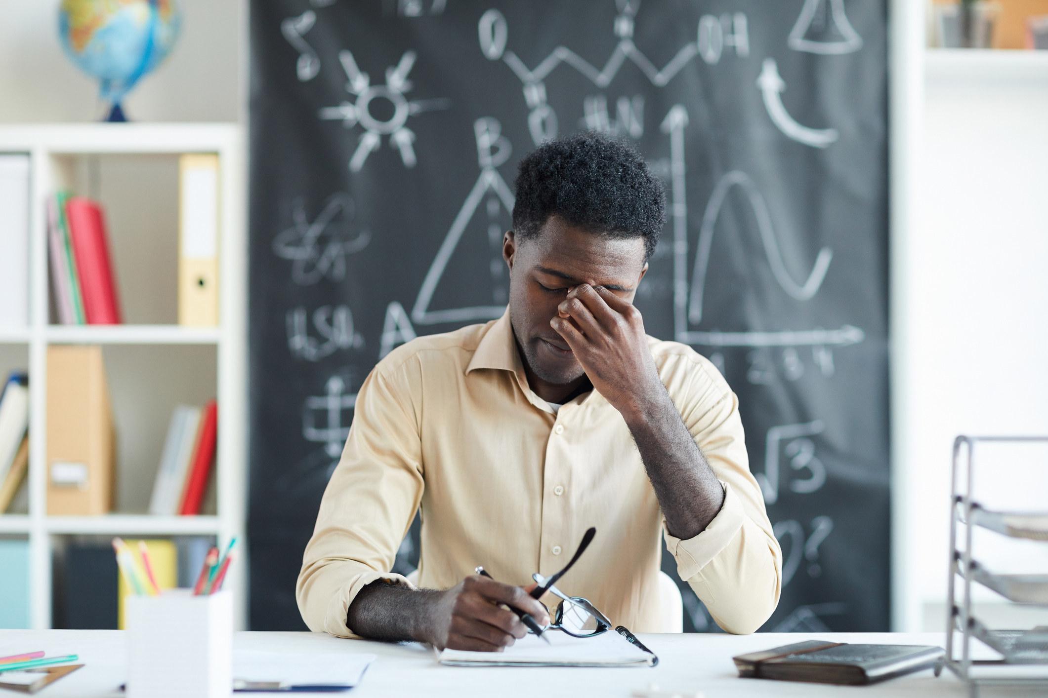 stressed teacher sitting at his desk