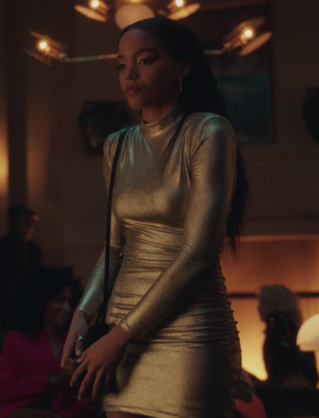 Zoya wears a tight fitted metallic long sleeve dress