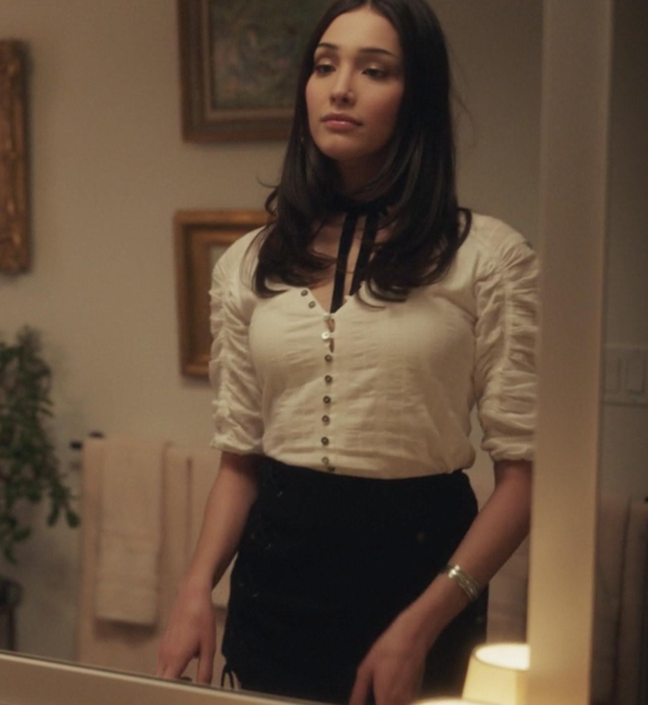 Zión Moreno wearing a button down blouse and skirt as Luna La