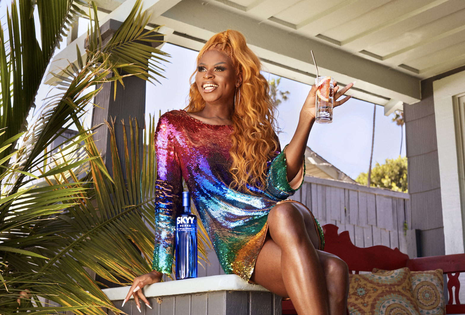 Symone lounging in a multicolored short sequined dress while sipping a glass of Skyy vodka