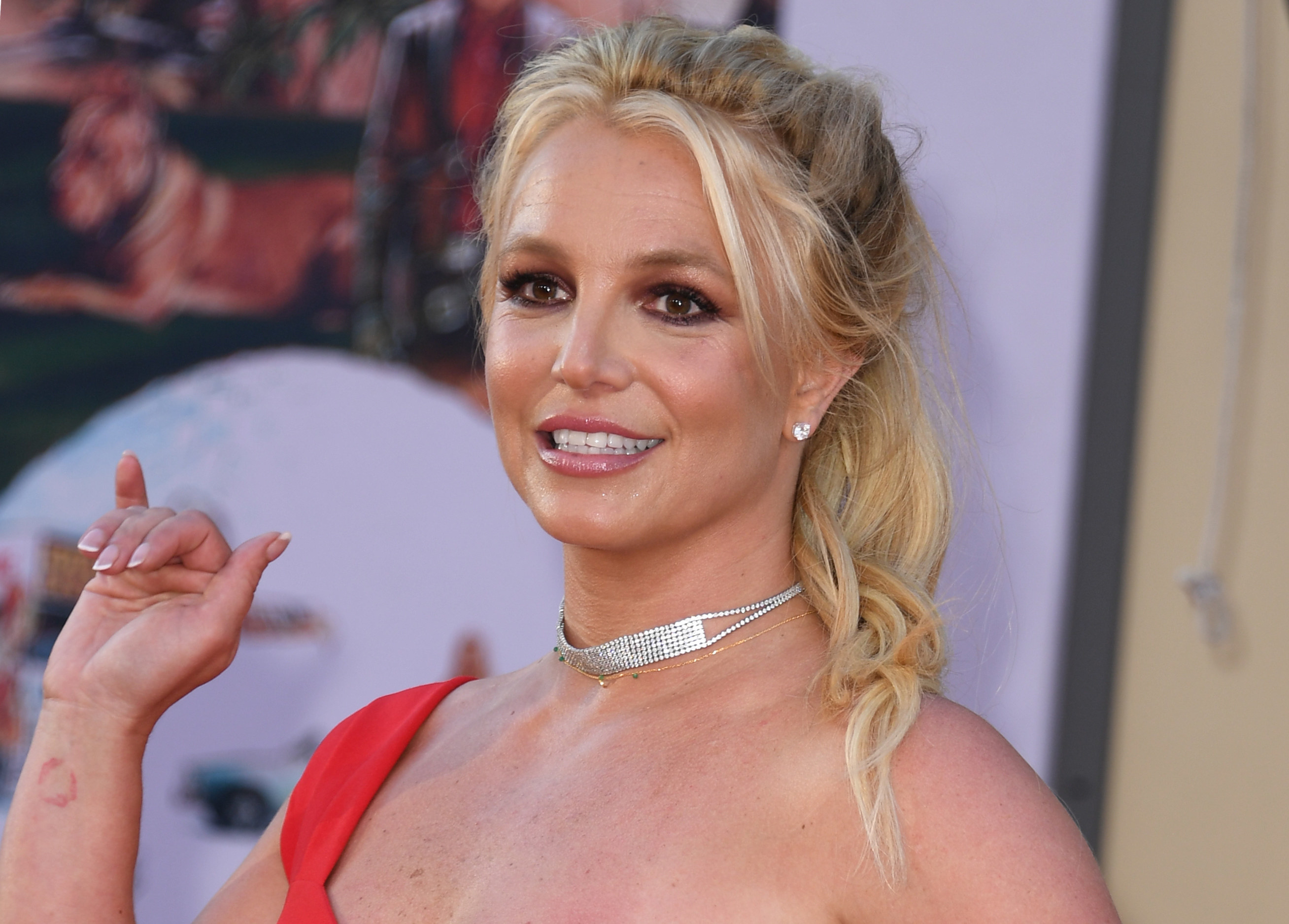 Britney Spears is photographed waving during a red carpet event