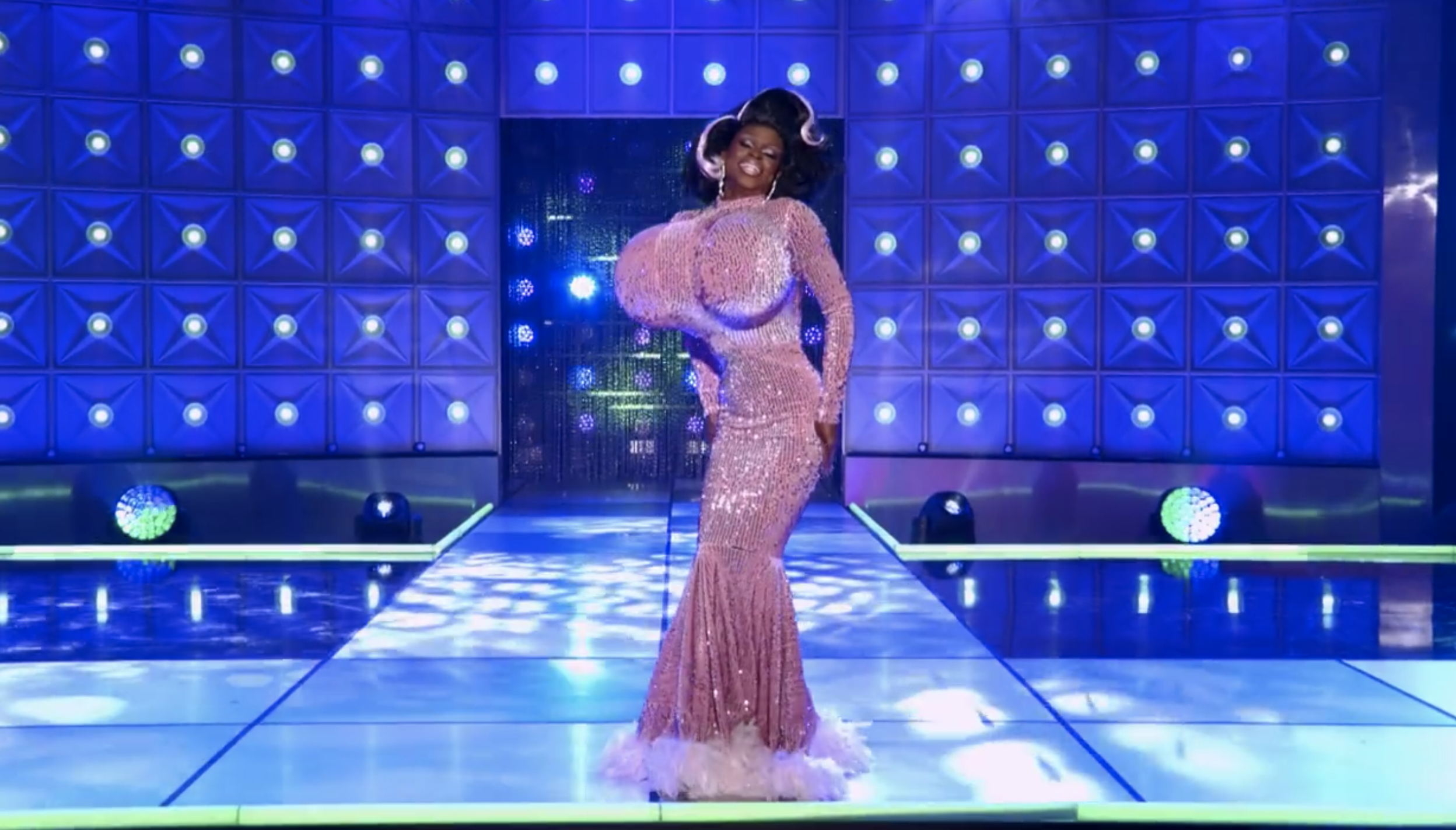 Symone on stage in a sequined and feathered gown