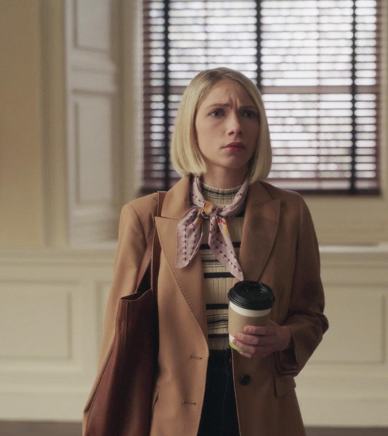Tavi Gevinson wearing a long coat and sweater as Kate Keller
