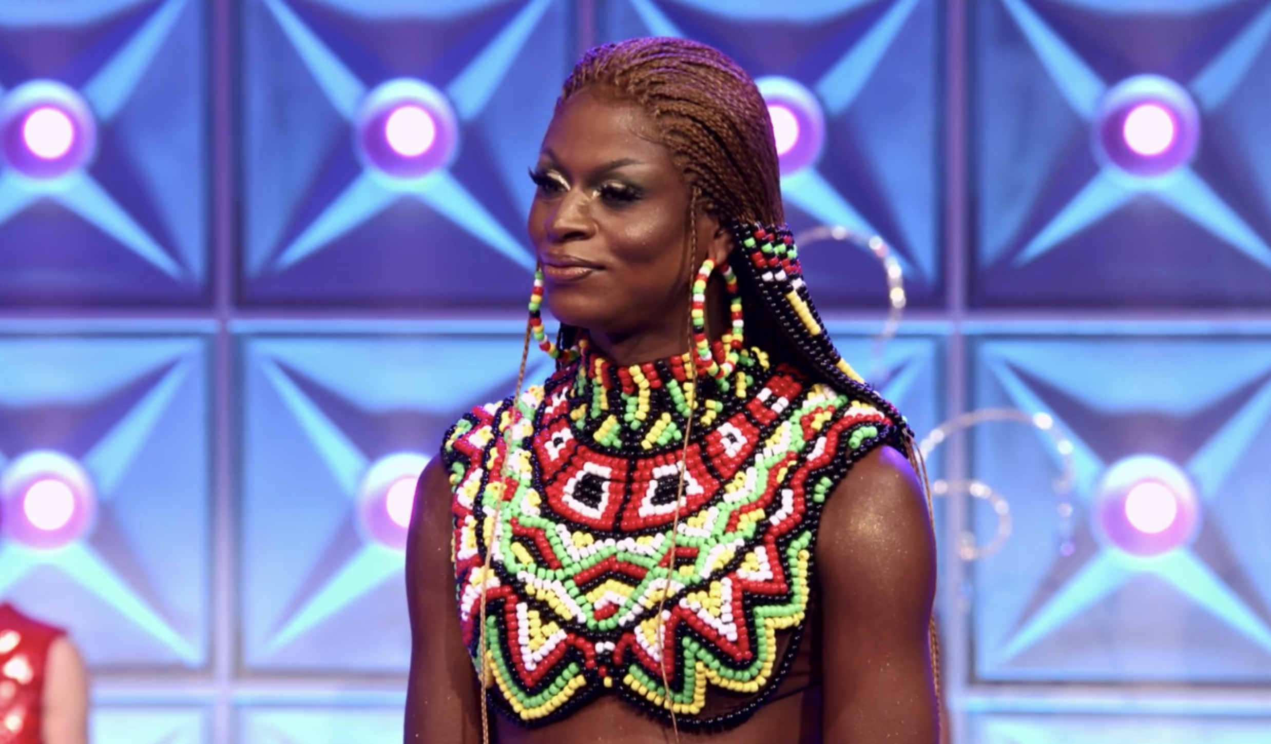Symone in a beaded collar neck piece with matching beaded hoop earrings and cornrows