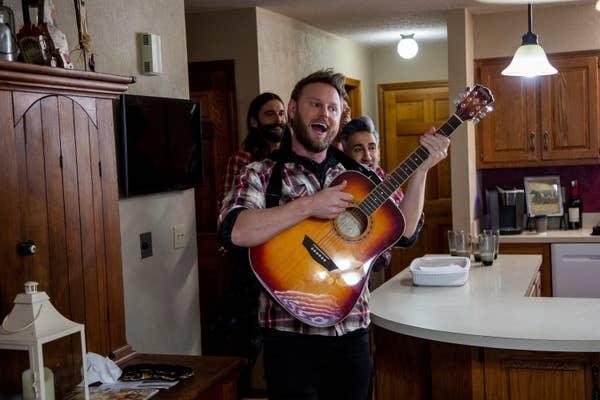 Bobby Berk playing the guitar in Queer Eye