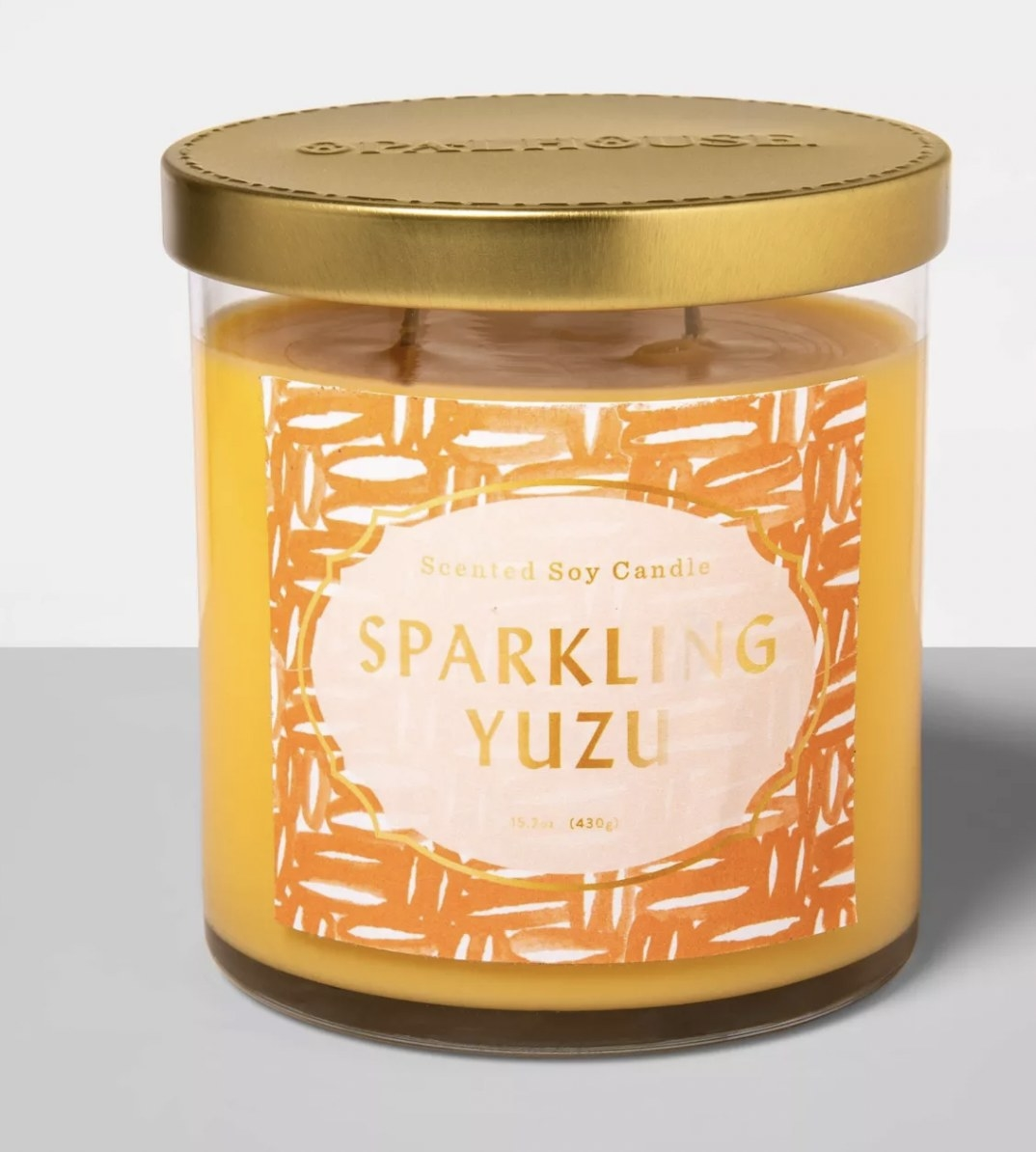 a yellow candle that reads sparkling yuzu