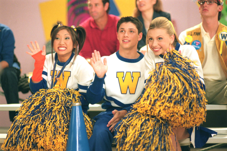 Brenda Song, Ricky Ullman, and Alyson Michalka sit in bleachers dressed as cheerleaders